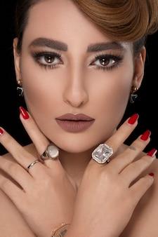 Modelo con peinado de fiesta y maquillaje de bronce con joyas de diamantes.