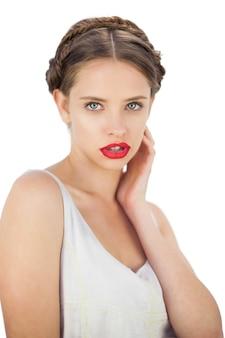 Modelo pensativo en vestido blanco posando con la mano en la mejilla