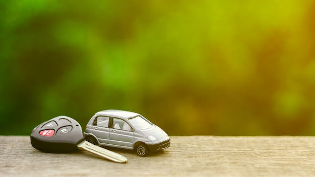 Modelo pequeño del coche con llaves en el escritorio de madera por la mañana.