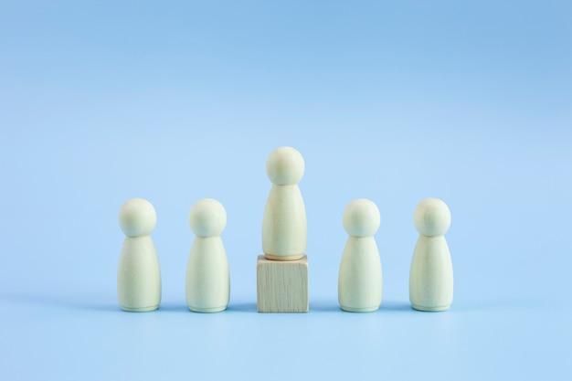 Modelo de persona de madera entre personas sobre fondo azul pastel