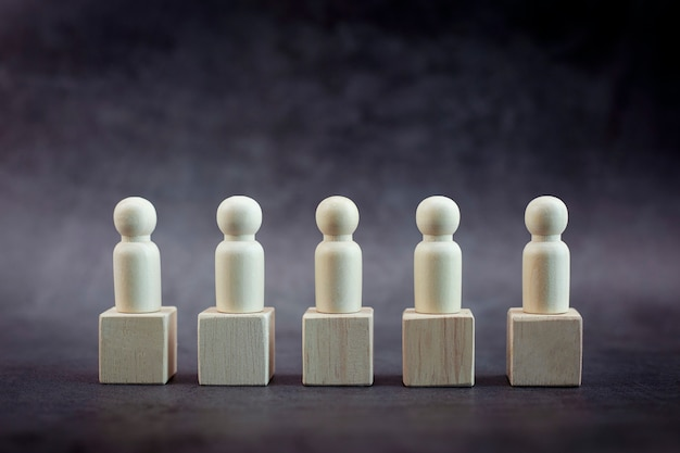 Modelo de persona de madera entre personas sobre fondo negro pastel concepto de liderazgo