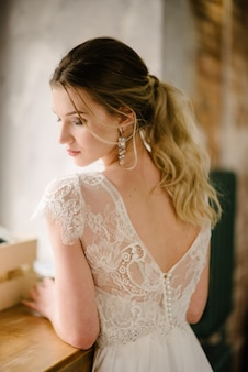 Modelo posando en un vestido de novia largo blanco en el interior junto a la ventana