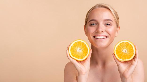 Modelo de primer plano sonriente con naranja y espacio de copia