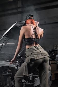 Modelo con ropa elegante de pie contra el capó abierto en el coche desmontado en el garaje.
