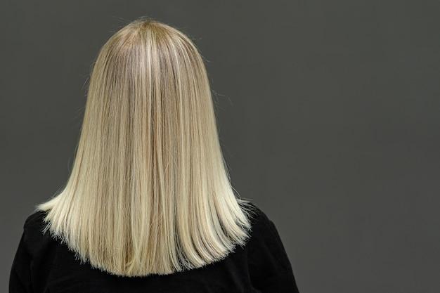 Modelo rubia con cabello lacio, mira desde atrás. resultado de aclarado del cabello. copia espacio