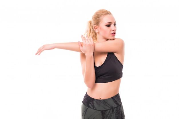 Modelo rubia delgada hace diferentes ejercicios en estudio vestida con ropa deportiva oscura