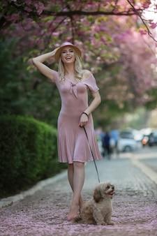 Modelo rubia con elegante sombrero en la cabeza durante un paseo por el parque de la ciudad