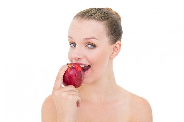 Modelo rubia muy divertida comiendo una manzana