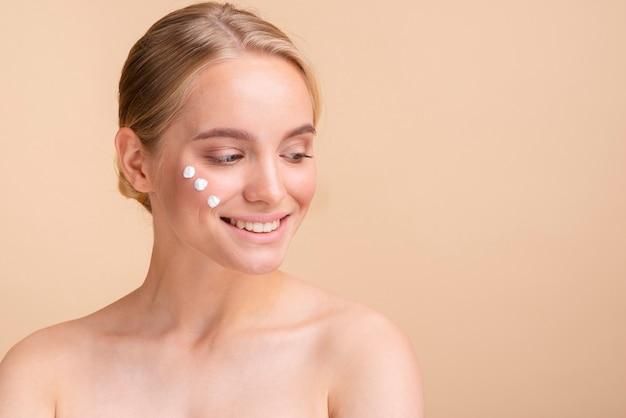 Modelo rubia de primer plano con crema para la cara mirando a otro lado