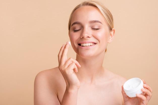 Modelo rubia de primer plano con crema para la cara