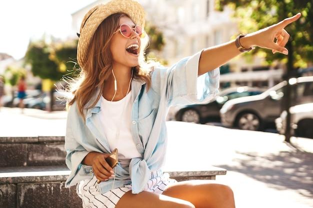 Modelo rubia en ropa de verano posando en la calle señalando algo