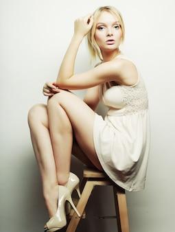 Modelo rubia sentada en un taburete