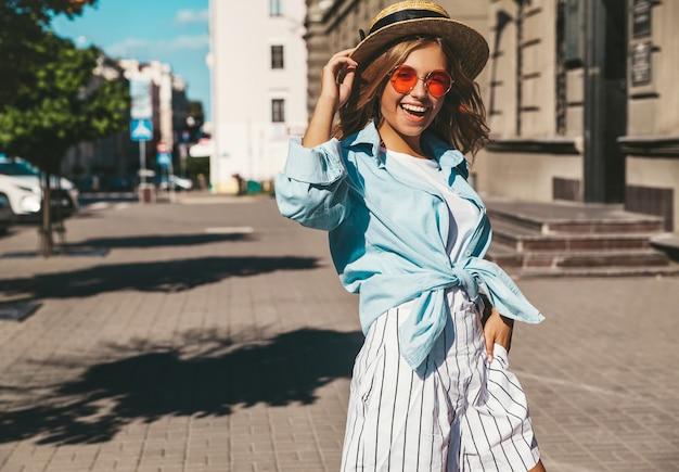Modelo rubia sonriente en ropa de verano posando en la calle. parpadeo