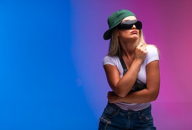Modelo rubio con gorra verde y gafas de sol se ve desagradable.