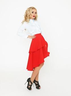 Modelo rubio con pelo de lujo y falda roja