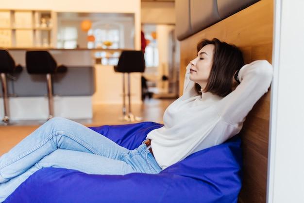 La modelo sexy de pelo corto descansa y toma una siesta diaria sentada en una silla azul en casa