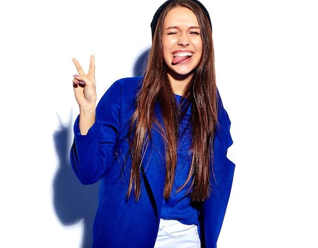 Modelo sonriente hermoso de la mujer morena del inconformista en el abrigo azul elegante aislado en blanco. mostrando su lengua y signo de paz