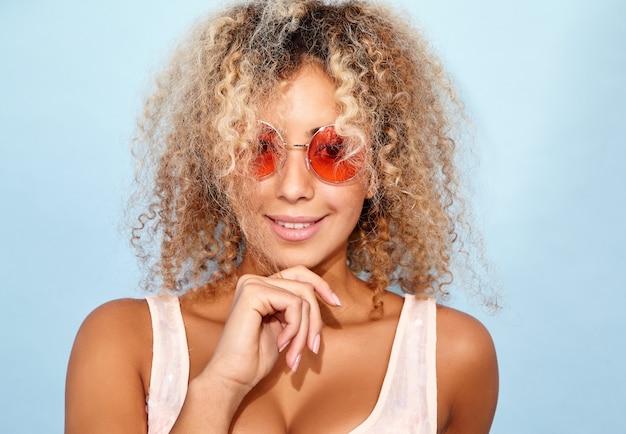Modelo sonriente en ropa de verano de moda en gafas de sol