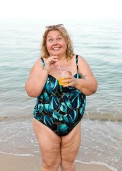 Modelo de talla grande de pie en la playa