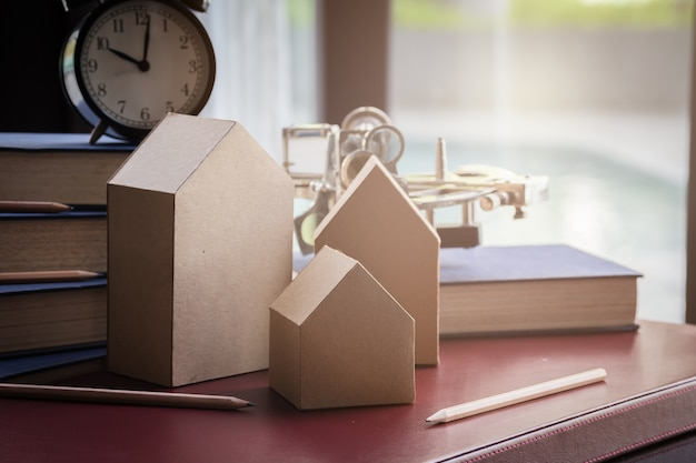 Modelo de tarjeta de la casa con libro y reloj de alarma con fondo borroso
