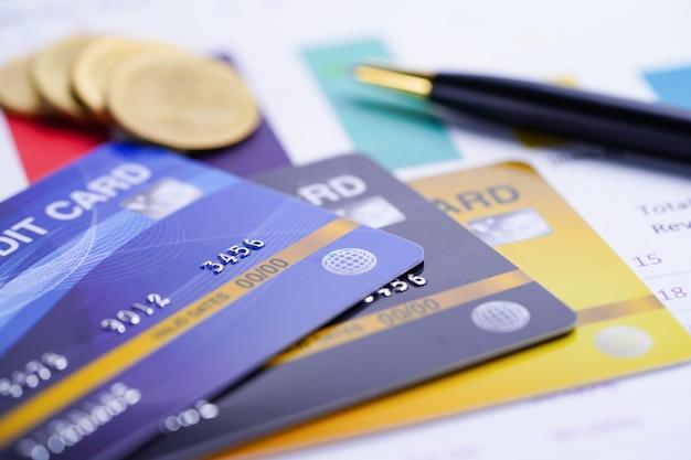 Modelo de tarjeta de crédito con monedas y bolígrafo.
