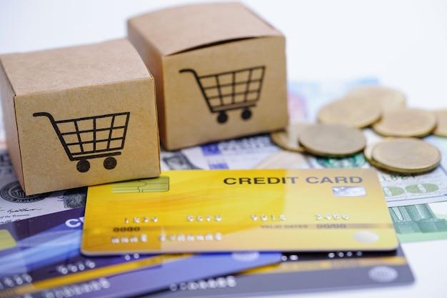 Modelo de tarjeta de crédito y monedas con caja de carrito de compras.