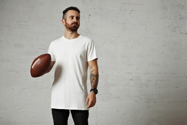 Modelo tatuado y barbudo en camiseta blanca lisa de manga corta sosteniendo una pelota de fútbol de cuero en la pared gris