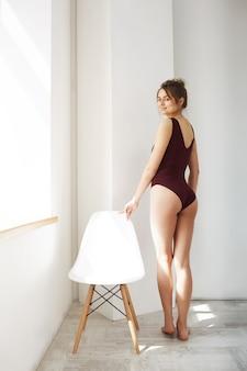 Modelo tierno hermoso joven en traje de baño que disfruta de las luces del sol de la mañana que retroceden cerca de silla sobre la pared blanca.