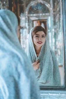 Modelo en trajes de oración frente a una mezquita histórica frente al espejo