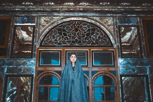 Modelo en vestido azul en una mezquita histórica