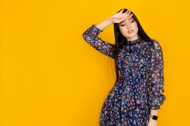 Un modelo con un vestido azul en una pared amarilla, con espacio para texto a la izquierda, con espacio de copia. concepto de tienda de ropa femenina, compras y moda