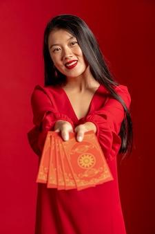 Modelo en vestido rojo mostrando tarjetas de año nuevo chino
