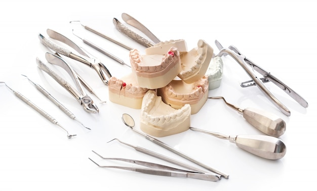 Modelo de yeso de mandíbulas y herramientas dentales.