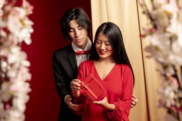 Modelos abrazados con regalo para año nuevo chino