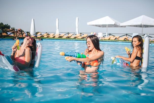 Modelos alegres y divertidos jugando en la piscina. sostienen pistolas de agua en las manos y lo usan. dos mujeres están en contra de la tercera. ellos sonríen y ríen
