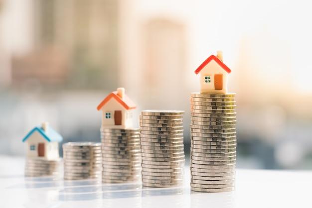 Modelos de casas en la parte superior de la pila de monedas con fondos de la ciudad.