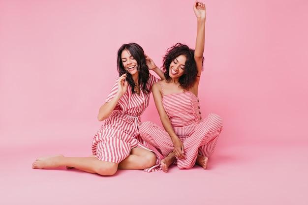 Modelos encantadores positivos en vestidos de rayas de diseñador posando. fotografía en interiores modelos de cuerpo entero sentados en el suelo.