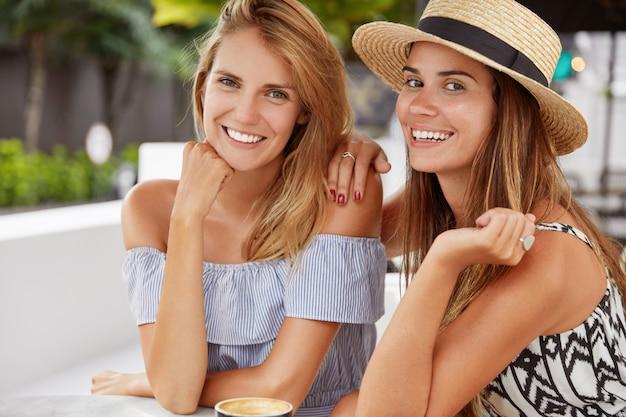 Las modelos femeninas alegres con amplias sonrisas se reúnen en el café, tienen una charla agradable con una taza de café, disfrutan de un buen descanso de verano, las mejores amigas se recrean juntas en el campo turístico, toman bebidas calientes