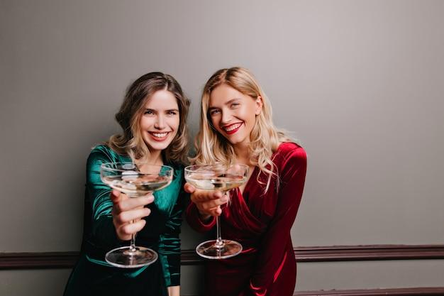Modelos femeninos guapos posando con copas en la pared gris. filmación en interiores de encantadoras damas en vestidos de terciopelo celebrando algo.
