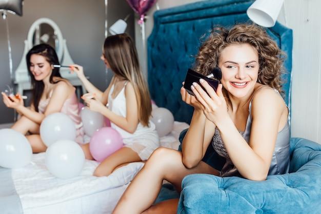 Modelos de moda que disfrutan reunirse en interiores, ayudando con el maquillaje.