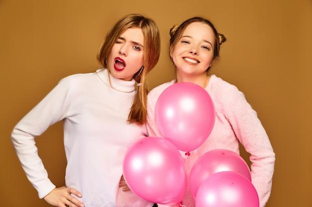 Modelos de mujeres con globos rosados en la pared dorada