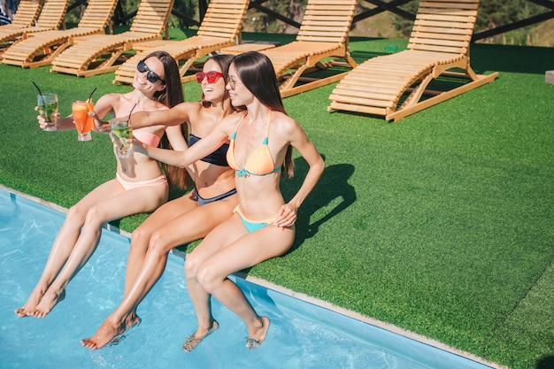 Las modelos se sientan al borde de la piscina y se relajan