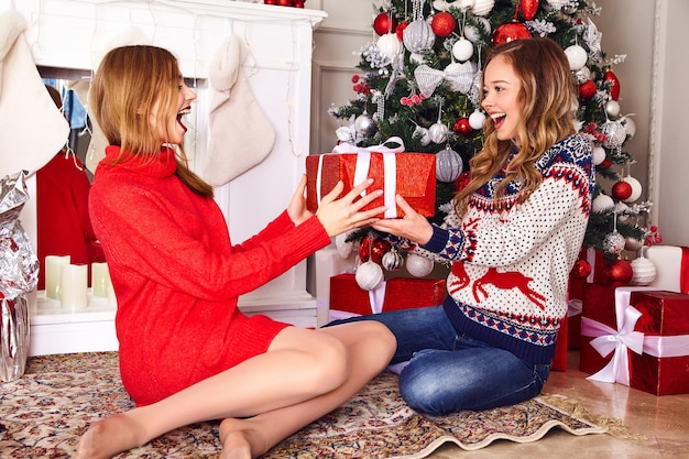 Modelos en suéteres de invierno cálido sentado cerca del árbol de navidad decorado en la víspera de año nuevo.