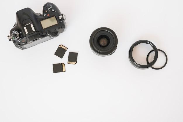 Moderna cámara réflex digital; tarjetas de memoria y lentes de cámara con anillos de extensión sobre fondo blanco