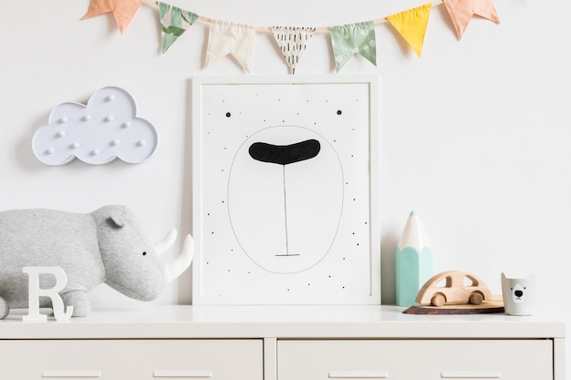 La moderna habitación escandinava para bebés recién nacidos con marco de fotos simulado, coche de madera, juguetes de peluche y nubes. colgando banderas de algodón y estrellas blancas. interior minimalista y acogedor con paredes blancas.