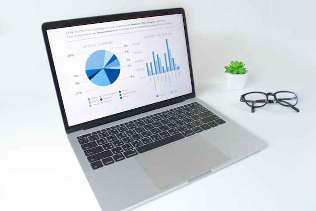 Moderna mesa blanca con ordenador portátil con informe de estadísticas financieras