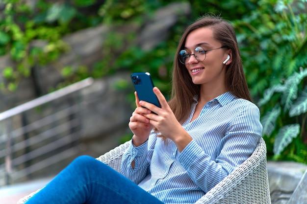 Moderna mujer milenaria inteligente casual feliz usando auriculares inalámbricos con smartphone para chatear y navegar en línea de forma remota