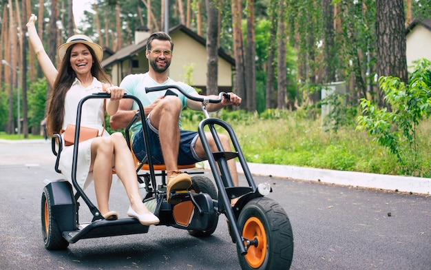 Moderna pareja de jóvenes turistas felices de vacaciones montando en bicicleta y divertirse juntos en el hotel del bosque