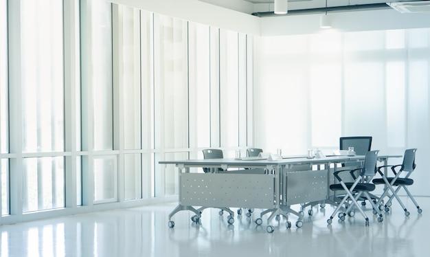 Moderna sala de reuniones interior con luz del atardecer desde ventanas de vidrio limpio