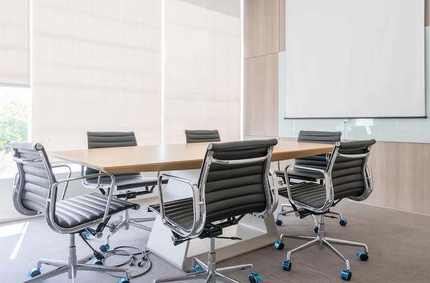 Moderna sala de reuniones con pantalla de proyección y mesa de conferencias.